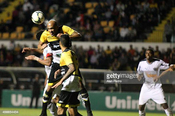 Souza of the Criciuma and Edcarlos of Atletico MG compete for a header during the between Criciuma and Atletico MG for the Brazilian Series A 2014 at...