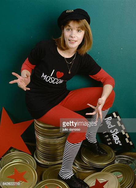 Soviet actress Vera Glagoleva wearing red leggings with a tshirt that reads I Love Moscow sits atop a pile of film reel containers at Mosfilm Studios...