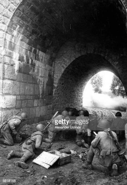 Soviet antitank gun crew firing at close range from under an archway during the Second World War