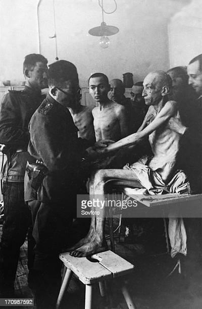 Soviet army surgeon examines an auschwitz concentration camp survivor, vienna engineer rudolf scherm, auschwitz, poland, february 1945.