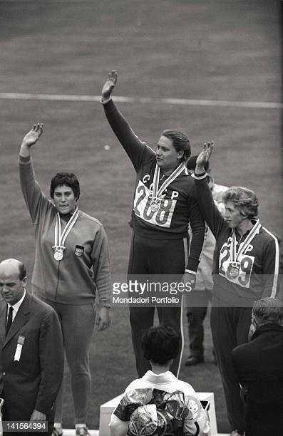 Soviet athletes Tamara Press and Galina Zybina greeting with a wave from the podium alongside East German athlete Renate GarischCulmberger during the...