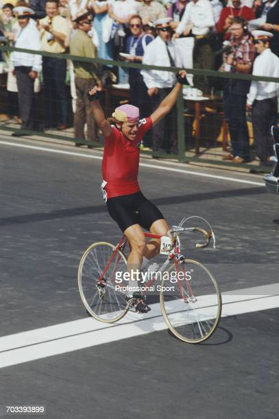 Soviet cyclist Sergei Sukhoruchenkov raises his arms in the air as he crosses the finish line in first place to win the gold medal for the Soviet...