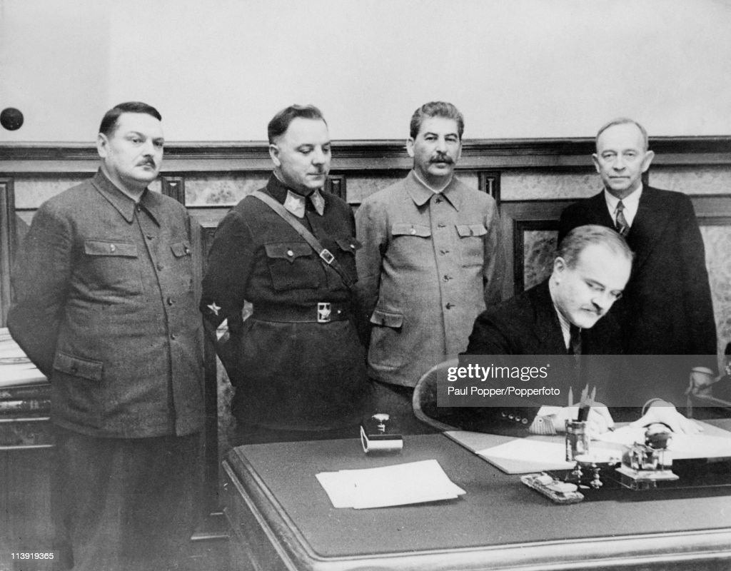 Soviet dictator Joseph Stalin (1879 - 1953) is present as Vyacheslav Molotov (1890 - 1986) signs a Mutual Assistance Agreement with a Finnish puppet state, in Moscow, December 1939. Standing, from left to right, are Andrei Zhdanov (1896 - 1948), Kliment Voroshilov (1881 - 1969), Stalin and Otto Wille Kuusinen (1881 - 1964), head of the Finnish Democratic Republic.