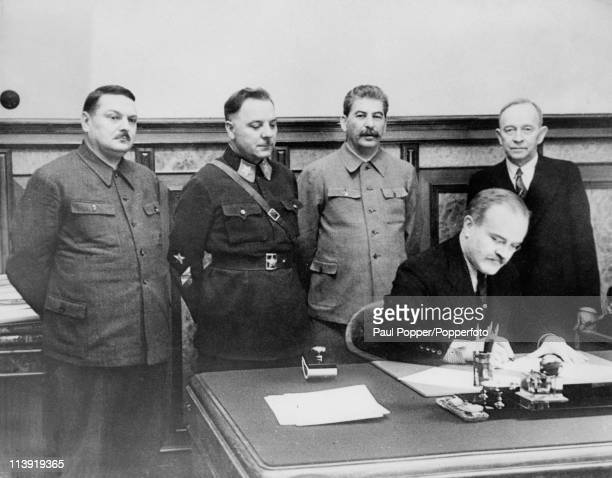 Soviet dictator Joseph Stalin is present as Vyacheslav Molotov signs a Mutual Assistance Agreement with a Finnish puppet state in Moscow December...