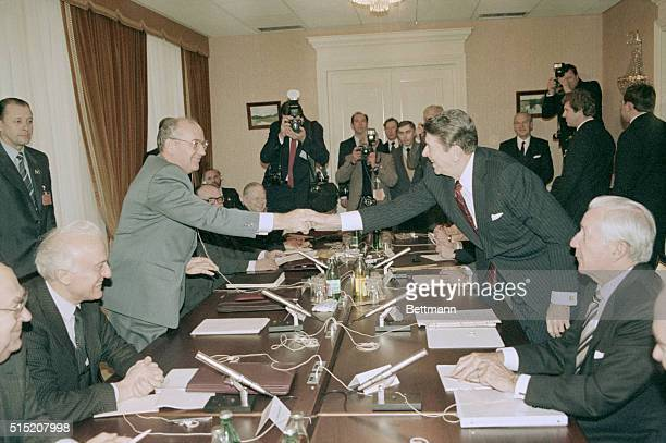 Soviet General Secretary Mikhail Gorbachev and U.S. President Ronald Reagan reach across the conference table to shake hands as the third summit...