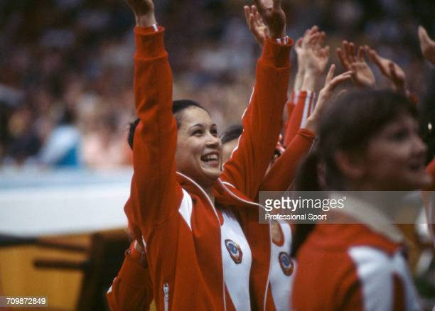 Soviet gymnast Nellie Kim raises her arms in the air in celebration as she views the scoring for the Soviet Union team during competition in the...