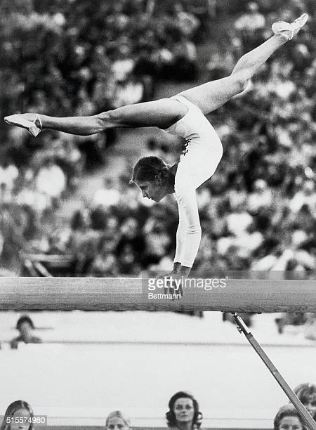 Soviet gymnast Olga Korbut performs a split handstand on the balance beam during the women's individual events competition at the 1972 Olympic Games...