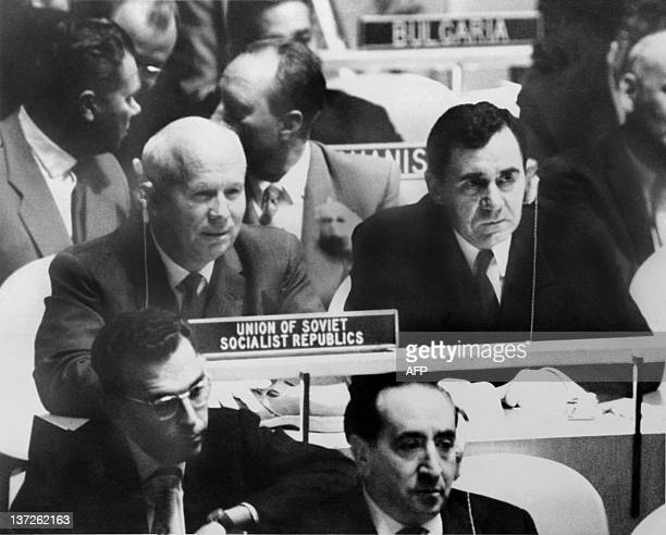 Soviet Head of State Nikita Khrushchev sitting at his desk at the United Nations 12 October 1960 in New York holds his shoe along with his Foreign...