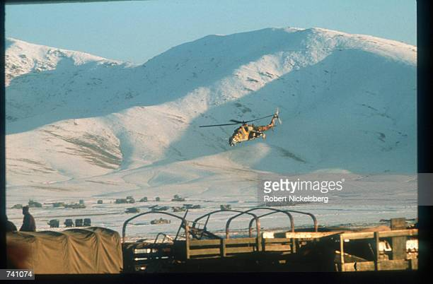 A Soviet helicopter gunship flies over equipment guarded by soldiers January 14 1989 near Kabul Afghanistan The end of Soviet military occupation...