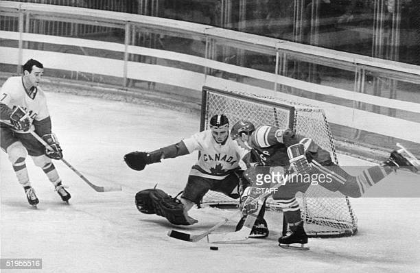 Soviet ice hockey player Anatoly Firsov tries to fire the puck past Canadian goalkeeper Wayne Stephenson 17 February 1968 in Grenoble during the...
