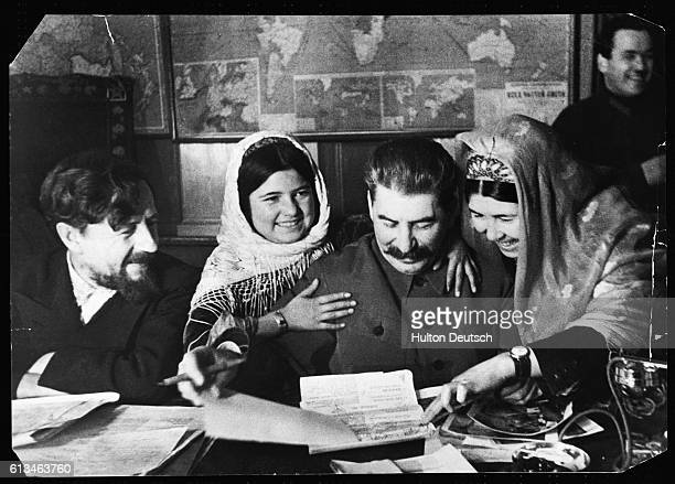 Soviet leader Joseph Stalin autographs photographs for 11yearold Mamlakat Nakhangova and Ene Geldiyeva members of a farming collective from...
