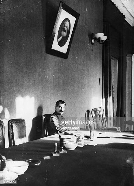 Russian political leader Joseph Stalin at work in his office with a portrait of Karl Marx hanging on the wall over his head