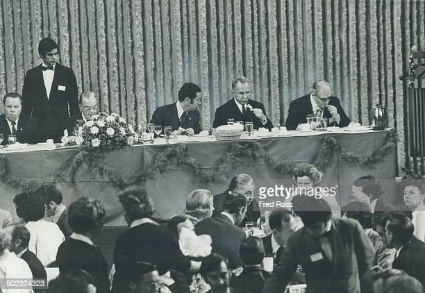 Soviet premier Alexei Kosygin eats dinner flanked by his interpreter Victor Sukhodryev and Gerard Filion president of the Canadian Manufacturers'...