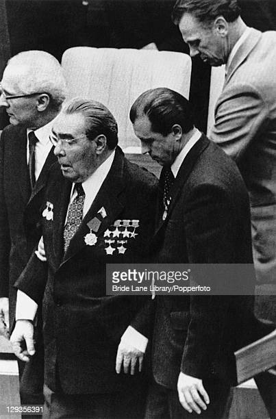 Soviet premier Leonid Brezhnev is lead from the podium by East German premier Erich Honecker after Brezhnev announced unilateral troop strength...