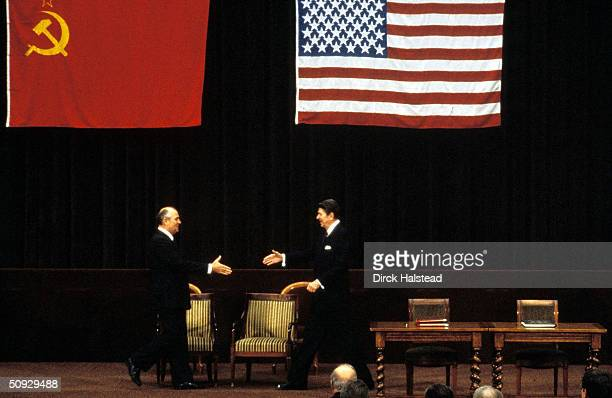 Soviet Premier Mikhail Gorbachev and U.S. President Ronald Reagan stride across the stage towards each other at their first summit meeting November...