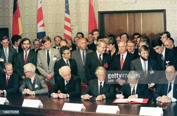 Soviet President Mikhail Gorbachev looks on while East German Prime Minister Lothar de Maiziere signs the treaty on German reunification 12 September...