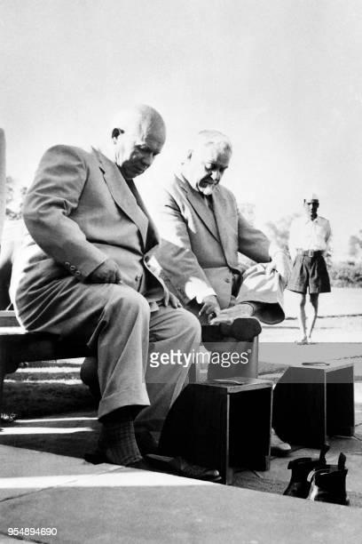 Soviet Prime minister Nikolai Bulganin and Soviet communist leader Nikita Khrushchev take off their shoes before a visit to the Gandhi Memorial in...