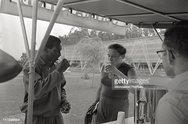 Soviet shot putter Tamara Press drinking with a black athlete during the Rome Olympic Games Rome 1960
