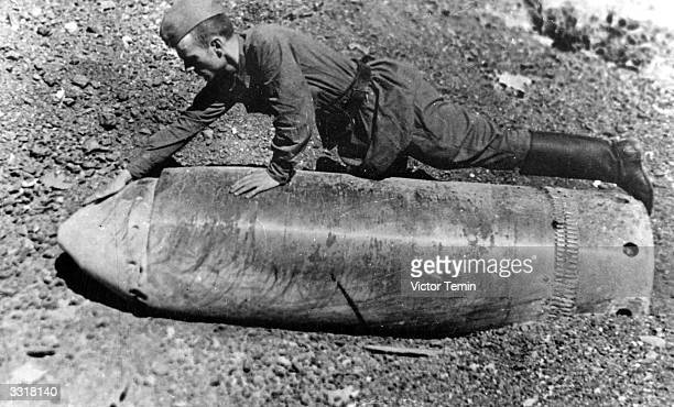 Soviet soldier examining a hugecalibre projectile which was fired at Stalingrad Russia by the Germans