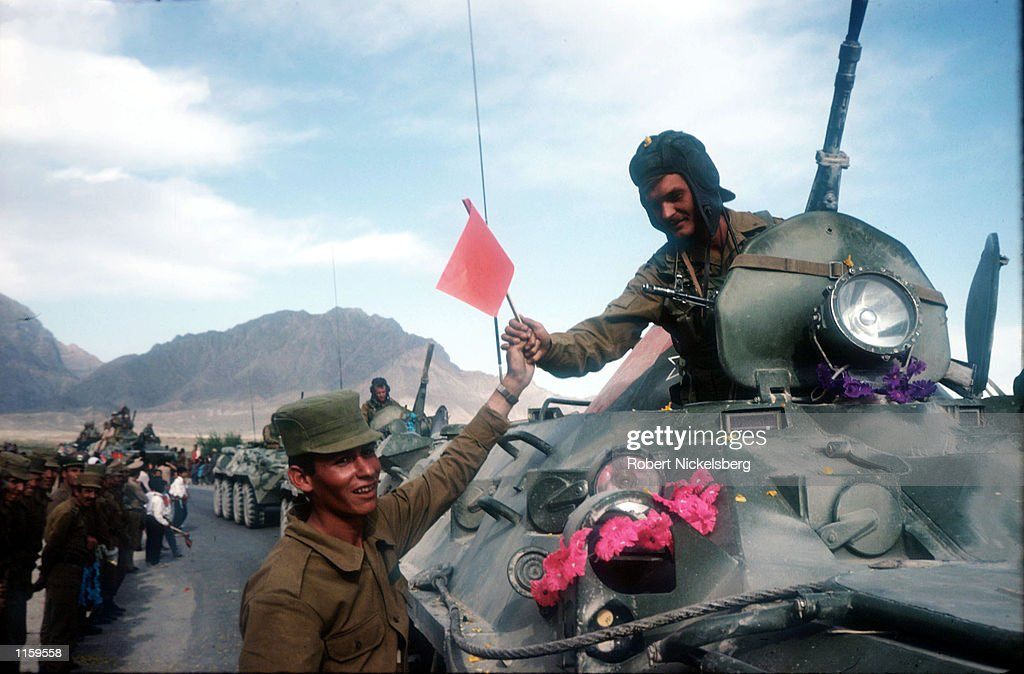 A Soviet soldier is handed a flag as Soviet troops withdraw May 15, 1988 from Kabul, Afghanistan. In May 1988 Afghanistan, Pakistan, the USSR, and the United States signed agreements providing for an end to foreign intervention in Afghanistan, and the USSR began withdrawing its forces.