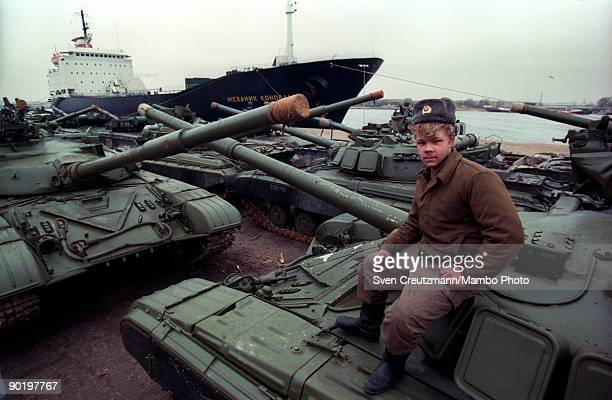 Soviet soldier sits atop a T80 tank as hundreds of tanks are lining up to be shipped back to the Soviet Union on January 26 in Rostock Germany The...