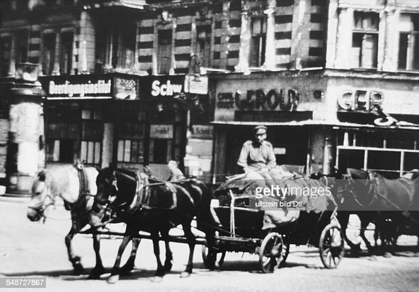 Soviet soldier with confiscated items on a horse cart in Berlin
