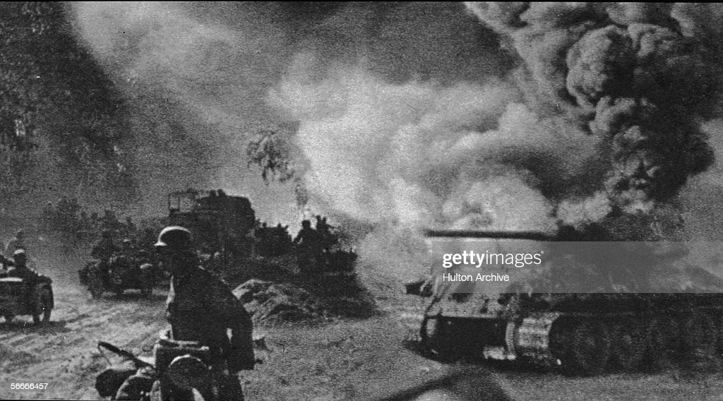 Soviet soldiers walk and drive past a burning T-34 medium tank during the Battle of Kursk, Russia, July 1943. Although the conflict between the Soviet and German forces barely lasted two months it is considered the largest armoured engagement in history.