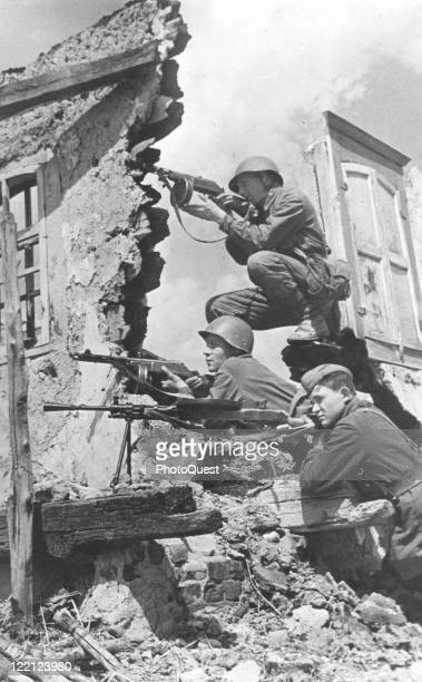 Soviet soldiers who have broken into the outskirts of a village occupied by the Germans take cover behind a wall and shoot, Ukraine, 1942. Action...