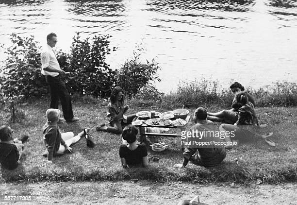 Soviet spy Eugene Ivanov gets his camera ready to take a picture during a picnic with a group of friends including model Catherine Keeler next to the...