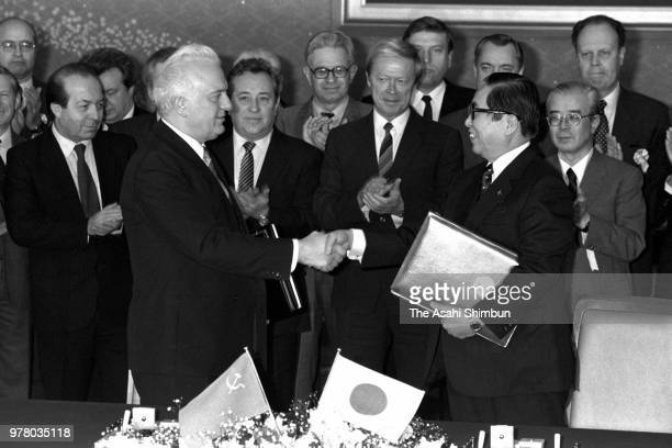 Soviet Union Foreign Minister Eduard Shevardnadze and Japanese Foreign Minister Sosuke Uno shake hands after exchanging signed documents following...