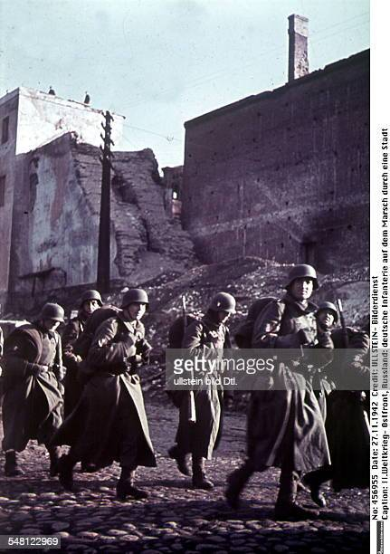 Soviet Union Russian SFSR World War II Soldiers of the 'Legion des volontaires francais' passing through a destroyed town on their advance towards...