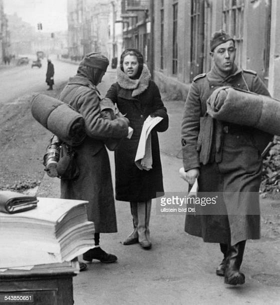 Soviet Union Ukrainian SSR Charkov Kharkov Kharkiv Ukranian woman is handing out a German newspaper called 'Eastern Front' to soldiers Photographer...