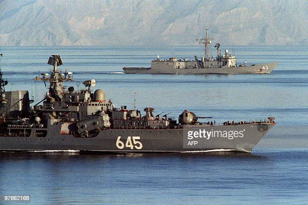 A Soviet warship passes alongside the US guided missile frigate USS Thach as it enters the Gulf off the coast of Oman November 21 1987 The Thach is...