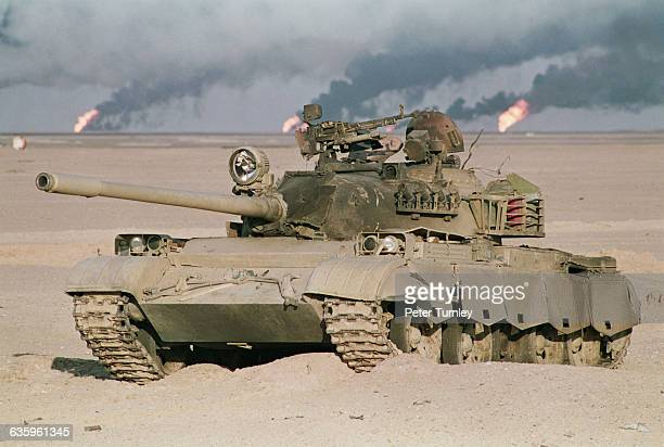 A Sovietbuilt Iraqi T55 tank sits in the desert at the end of the Gulf War Oil wells burn in the background