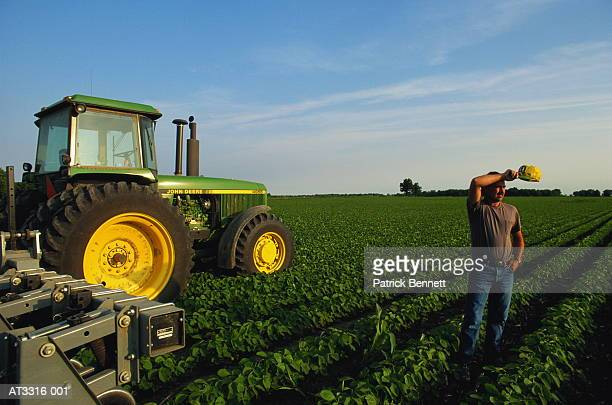 Soya bean farmer in field with tractor, wiping brow, Indiana, USA