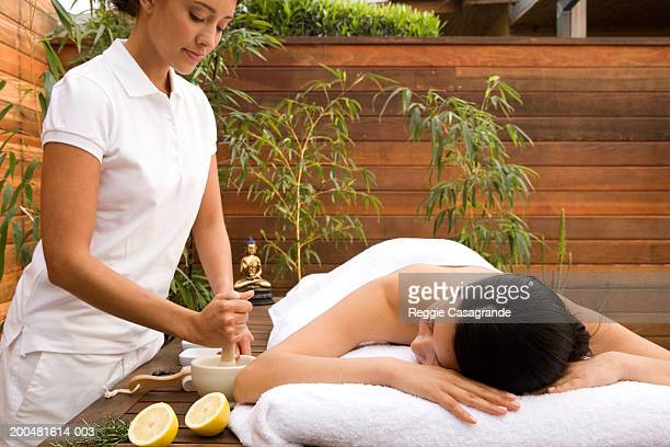 Spa attendant beside young woman on massage table