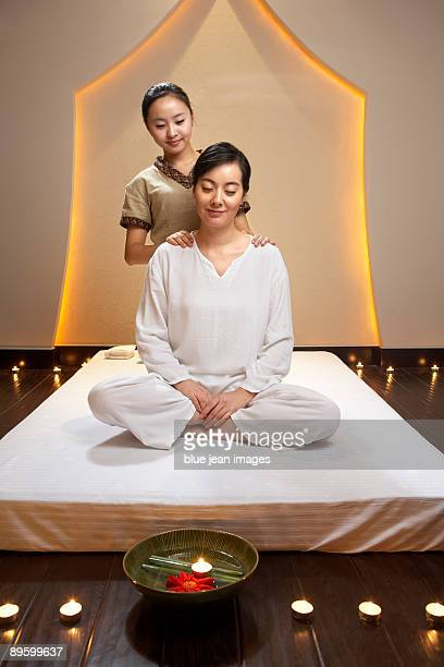 Spa attendant giving a shoulder massage to woman