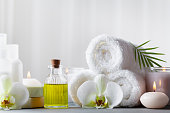 Spa, beauty treatment and wellness background with massage oil, orchid flowers, towels, cosmetic products and burning candles.