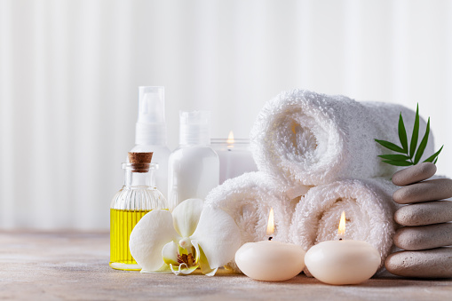 Spa, beauty treatment and wellness background with massage pebbles, orchid flowers, towels, cosmetic products and burning candles. 1134916892