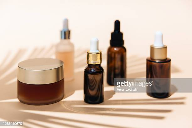 spa cosmetics in brown glass bottles on broun background. copy space for text. beauty blogger, salon therapy, branding mockup, minimalism concept. various facial massage oils for spa treatment. - cosmetics stock pictures, royalty-free photos & images