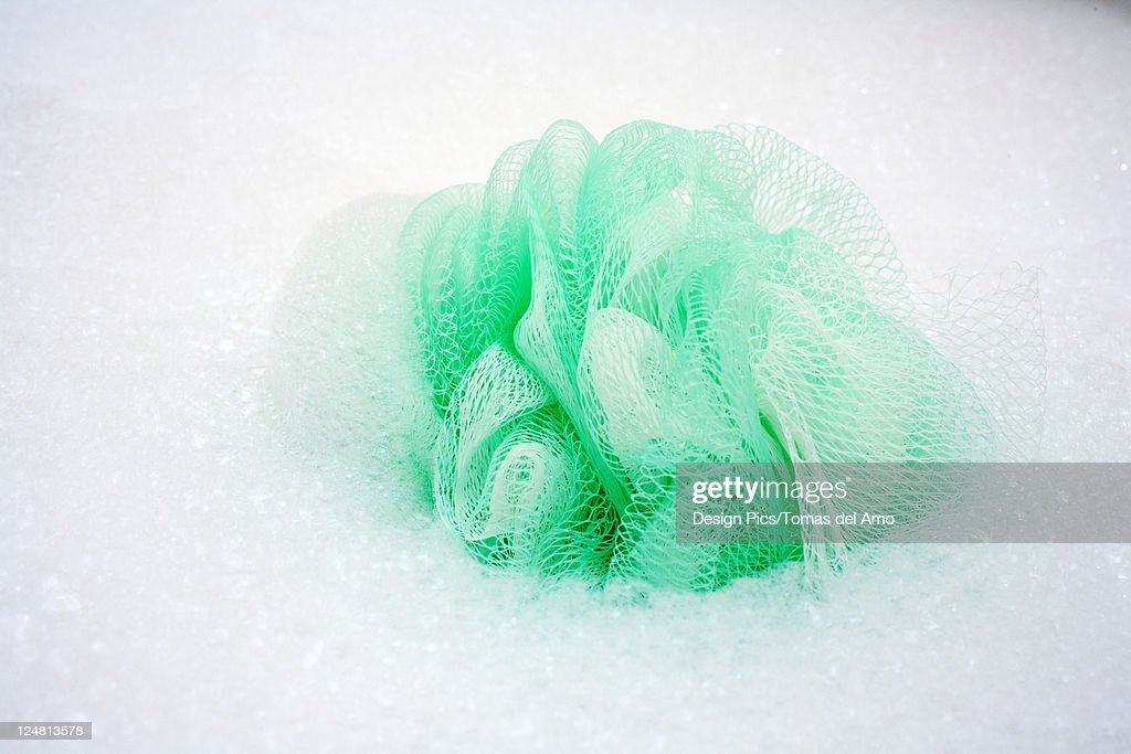 Spa elements, Green loofa with lots of bubbles in bathtub. : Stock Photo