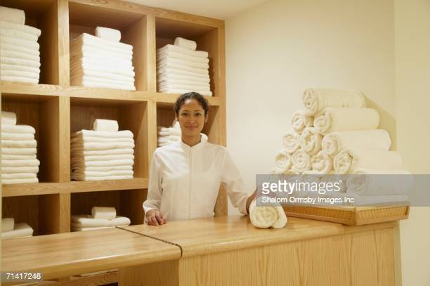 Spa employee behind counter with rolled towels