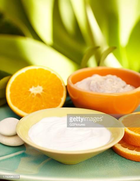 Spa exfoliation salt scrub, moisturizer orange slices on a plate