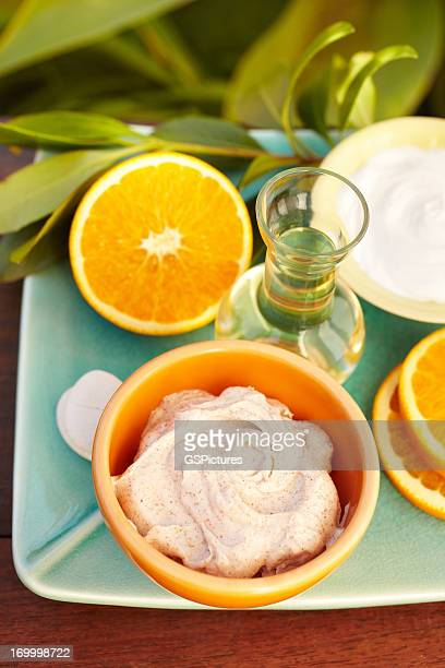 Spa exfoliation salt scrub, oranges and moisturizer on a plate