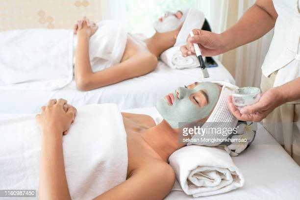 spa face mask, young beautiful girl in mask for face relaxing in spa salon - thai massage stockfoto's en -beelden