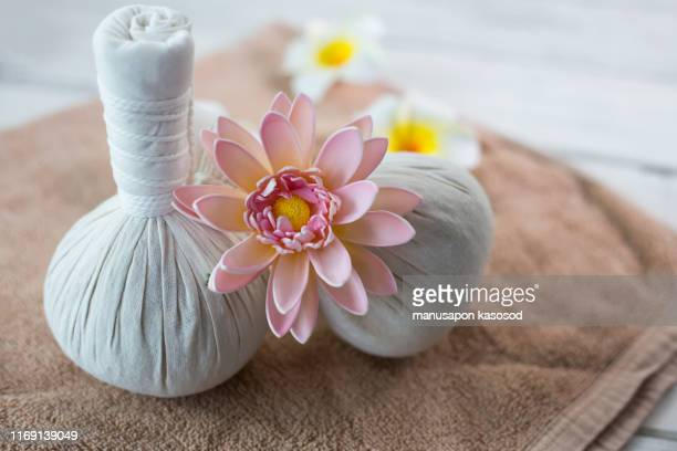 spa herbal compressing ball with candle and orchid. - thai massage stockfoto's en -beelden