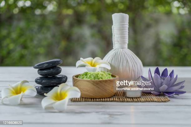 spa herbal compressing ball with herbs ,plumeria flowers lotus and candle - thai massage stockfoto's en -beelden
