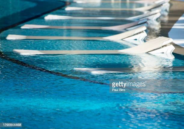 spa pool with floating flowers and lounge chairs. spa concept - tourist resort stock pictures, royalty-free photos & images