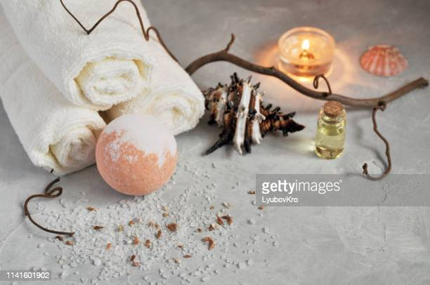 Spa relax concept. White Terry towels, stones, a candle and a bomb for a bath of sea salt on a gray textured background.