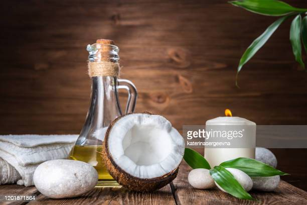 spa still life with coconut, massage oil and candle on a wooden background - coconut oil stock pictures, royalty-free photos & images